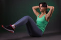 Beautiful sporty woman fitness woman doing exercise on a dark background with green backlight abdominal muscles Stock Photos