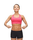Beautiful sporty woman pointing at her six pack picture of Stock Photography
