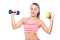Beautiful sporty young woman with a dumbbell and an apple agains Royalty Free Stock Photo