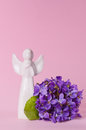Beautiful spring flowers bouquet of violets and little white angel porcelain figurine, viola on a pink background Royalty Free Stock Photo