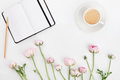 Beautiful spring Ranunculus flowers, empty notebook and cup of coffee on white desk from above. Greeting card. Breakfast. Flat lay Royalty Free Stock Photo