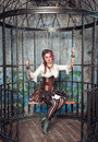 Beautiful steampunk woman in the cage with pink hair sitting metal Stock Images