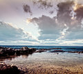 Beautiful stony coast photo of rocky beach dramatic sunset cloudy sky stunning seascape summertime vacation travel and tourism Stock Photography