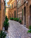 Beautiful alley at an old mediterranean village with rustic stone houses Royalty Free Stock Photo