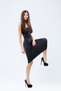 Beautiful striding girl in tight black dress isolated on white background Stock Photo