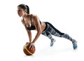 Beautiful strong woman doing push up on ball isolated on a white background. Royalty Free Stock Photo