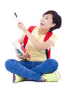 Beautiful student asian girl holding pen and sitting on floor over white background Stock Photos