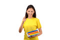 Beautiful student with books pointing in front to you attractive girl yellow t shirt holding isolated on white Royalty Free Stock Photography