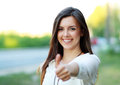 Beautiful student girl in white blouse lifts thumb upwards against green of summer park Stock Photos