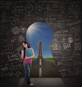 Beautiful student standing in class with road to success via keyhole Royalty Free Stock Photos
