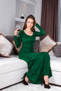 Beautiful stylish girl with long hair in luxury interior posing in stunning evening dress with glass of red wine in her hand. Read Royalty Free Stock Photo