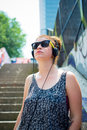 Beautiful stylish modern young woman listening to music in the city Stock Image