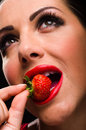 Beautiful stylish woman eating a strawberry juicy red Royalty Free Stock Image
