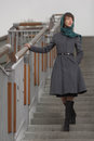Beautiful stylish woman in grey coat standing on stairs outdoors Stock Photo