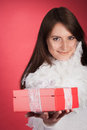 Beautiful stylish woman with a red gift box in glamorous feathery outfit holding out for christmas or valentines lovely smile Stock Photo