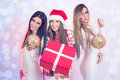 Beautiful stylish women celebrating new year three young caucasian holding decoration and gift box against blurry bokeh background Stock Photography