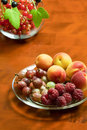 Beautiful summer berries raspberries gooseberries apricots on a plate Stock Photos