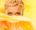Beautiful summer girl young woman hiding behind big yellow flower Stock Photo