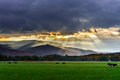 Beautiful sun rays through the clouds over mountains Royalty Free Stock Photo