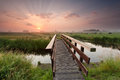 Beautiful sunrise over bike bridge in farmland Royalty Free Stock Photo