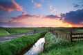 Beautiful sunrise over farmland river and meadows in Royalty Free Stock Image