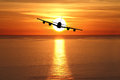 Beautiful sunset with airplane over the sea Royalty Free Stock Images