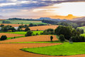 Beautiful sunset over countryside landscape of rolling hills with sun beams piercing sky and lighting hillside Stock Photos