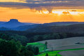 Beautiful sunset over countryside landscape of rolling hills with sun beams piercing sky and lighting hillside Royalty Free Stock Photo