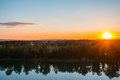Beautiful Sunset over the lake with forest reflection in water Royalty Free Stock Photo