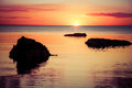 Beautiful sunset over water, with rock silhouettes. Royalty Free Stock Photo