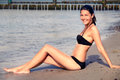 Beautiful svelte young woman in a bikini relaxing sitting on the sand sunbathing on the beach during her summer vacation side view Stock Photo