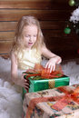 Beautiful sweet girl sits near a Christmas tree. She opens the gift. Royalty Free Stock Photo