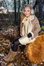 Beautiful sweet little girl dressed in a sheepskin coat and boots sitting on the trunk and in the background Royalty Free Stock Photo