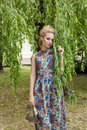 Beautiful sweet tender girl blonde with blue eyes stands near a tree with long branches with a sprig of flowers in her hands Royalty Free Stock Photo