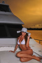 Beautiful swimsuit model wearing white bikini and hat posing on deck of luxury yacht Royalty Free Stock Photo