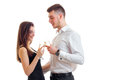 Beautiful tall guy in a white shirt standing next to an attractive girl, and they drink champagne from glasses