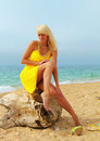 Beautiful tanned blonde girl on the sea in a yellow dress beach Stock Photos