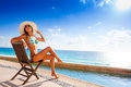 Beautiful tanned woman with sunglasses sunbathes under bright sun while sitting on wooden chair on stoned pier near to the ocean Stock Photos