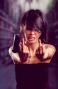 Beautiful tattooed girl with attitude holding gun angry and showing middle finger Royalty Free Stock Photography