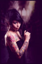 Beautiful tattooed girl with attitude holding guns in black dress pointing up selective focus Royalty Free Stock Images