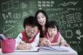 Beautiful teacher help children to write in class