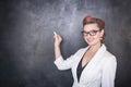 Beautiful teacher with piece of chalk on blackboard background