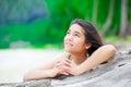 Beautiful teen girl on beach praying by driftwood log Royalty Free Stock Photo