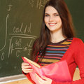 Beautiful teen girl high achiever in classroom near desk with fo