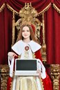 Beautiful teen girl holding laptop sitting in vintage armchair Royalty Free Stock Photo