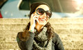 Beautiful teen girl talking on the phone smiling warm filter with black hat and sun glasses and Stock Photos