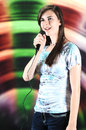Beautiful teen soloist a vertical image of a happily singing into a microphone Royalty Free Stock Photos