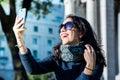 Beautiful teenage girl with dark hair and sun glasses taking selfies and laughting - close shot Royalty Free Stock Photo