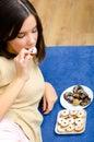 Beautiful teenage girl eating chocolate cookies at home Royalty Free Stock Photo
