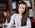 Beautiful teenage girl with female classmate in portrait of background at library Royalty Free Stock Images